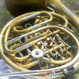 A photo of a French Horn laid down on the grass next to sheet music on the grounds of Rideau Hall