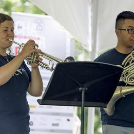 Deux musiciens de cuivres se produisent au Chamberfest 2018 sur le terrain de Rideau Hall, jouant respectivement de la trompette et du cor d'harmonie.