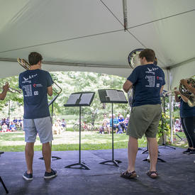 A picture taken from behind a troupe of musicians as they play for an audience on the grounds of Rideau Hall.
