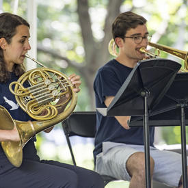 Two brass musicians perform at Chamberfest 2018 on the grounds of Rideau Hall, playing the French horn and trombone respectively.
