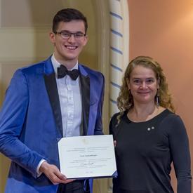 Sven Stammberger tient son certificat et pose pour une photo aux côtés de la gouverneure générale.