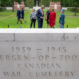 A photo of a stone marking the Bergen-op-Zoom Canadian War Cemetery, the Governor General in the background.