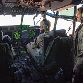 La gouverneure générale Julie Payette regarde un pilote et son co-pilote à l'oeuvre dans un cockpit d'avion.