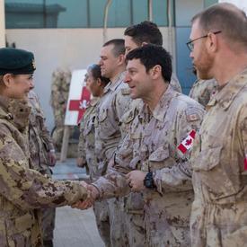 La gouverneure générale Julie Payette serre la main de membres des Forces armées canadiennes.