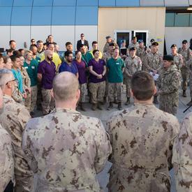 La gouverneure générale Julie Payette s'adresse à des dizaines de membres des Forces armées canadiennes rassemblés en cercle autour d'elle.