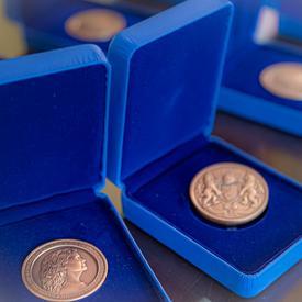 Trois médailles de la Mention élogieuse académique du Gouverneur général pour l'ensemble du Canada exposées dans des boîtes bleues ouvertes sur une table.