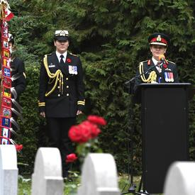 The Governor General of Canada, in a canadian army uniform, is speaking at a podium, in a cemetary during a Remembrance Day Commemoration in Belgium. Her female Aide-de-camp is standing on her right side.