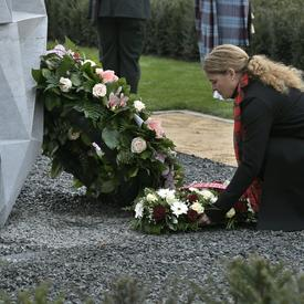 The Governor General of Canada is laying a wreath of flower on a tomb in a cemetary.