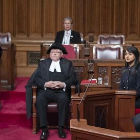 La gouverneure générale est assise dans la Chambre du Sénat et l'huissier du bâton noir reconnaît sa présence.