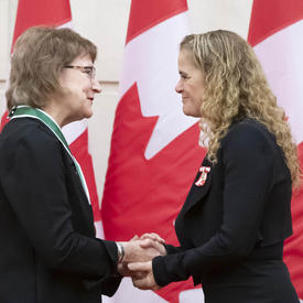Charlotte Hrenchuk is shaking hands with the Governor General.