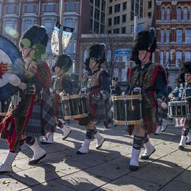 Les tambours, vêtus d'uniformes militaires composés d'un kilt et de tartan, marchent et jouent.