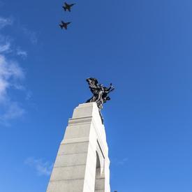 Cinq avions, dans un ciel bleu vif, survolent le Monument commémoratif de guerre du Canada.