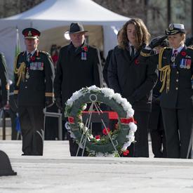 La gouverneure générale salue alors qu'elle se tient devant une couronne.  Son fils se tient à sa gauche.  Derrière eux se trouve une rangée de personnes, dont le chef d'état-major de la Défense, le général Jonathan Vance.