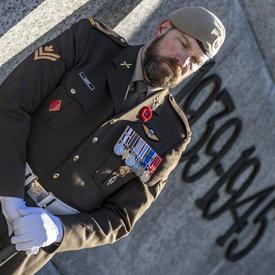 Un gros plan d'une sentinelle au garde-à-vous devant le Monument commémoratif de guerre du Canada.  Les dates 1939-1945 sont visibles derrière lui.