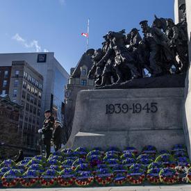 Des centaines de couronnes sont déposées à la base du Monument commémoratif de guerre du Canada.  Deux sentinelles se tiennent au garde à vous.