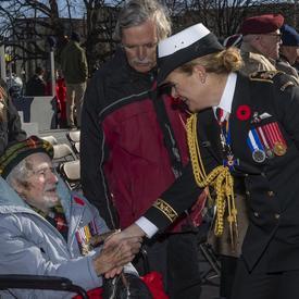 La gouverneure générale serre la main d'un ancien combattant en fauteuil roulant.