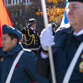 Des militaires tenant des drapeaux défilent au premier plan.  Entre leurs rangs, nous voyons la gouverneure générale saluer ainsi que Mme Anita Cenerini.