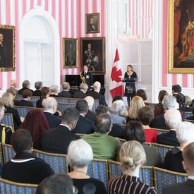 The Governor General, Julie Payette, stands at a podium and delivers a speech to a seated crowd of around 200 people.