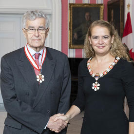 The Governor General, Julie Payette, stand next to Louis LeBel, retired justice of the Supreme Court of Canada. Both are wearing the Order of Canada isignias.