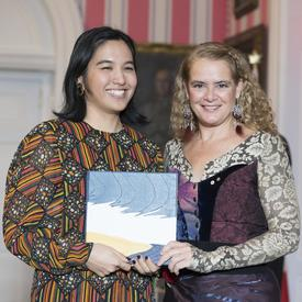 Jill Tamaki and Governor General Julie Payette stand side-by-side.  They are holding a leather bound book and smile to camera.