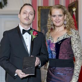 Michaël Trahan se tient aux côtés de la Gouverneure générale Julie Payette.  Ils tiennent un livre relié en cuir et sourient à la caméra.