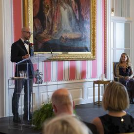 Mario Brassard stand at a podium.  The Governor General, Julie Payette, sit on his left.