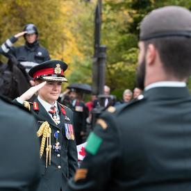 La Gouverneure générale Julie Payette, en uniforme militaire, salue.  Les militaires se tiennent au premier plan.