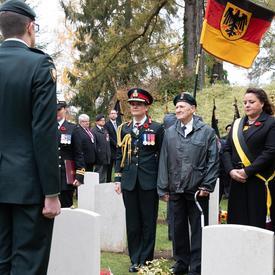 La gouverneure générale se tient devant une tombe blanche.  À sa droite, M. George Barkhouse.