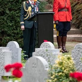 La gouverneure générale Julie Payette se tient à un podium.  Au premier plan, des pierres tombales blanches.  Derrière elle, à sa droite, un agent de police montée en rouge se tient au garde-à-vous.