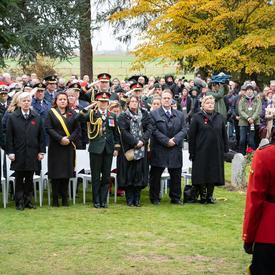 Une foule nombreuse se tient devant leurs chaises.  La gouverneure générale Julie Payette est debout au centre, en uniforme militaire, elle fait un salue militaire.