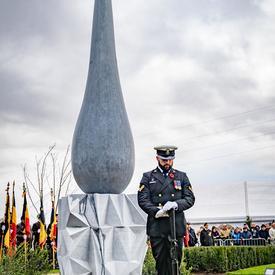 Un militaire se tient devant un monument, les yeux tournés vers le sol.  La base du monument a un motif triangulaire angulaire, le sommet est une grande larme.