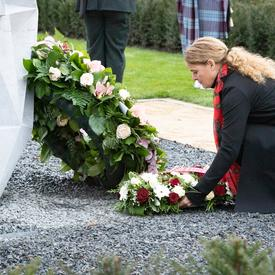 The Governor General kneels to place a wreath, decorated with flowers, at the base of a monument.
