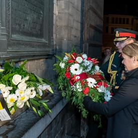 The Governor General of Canada is laying a wreath of flower at a wall monument at night with the help of a military member.