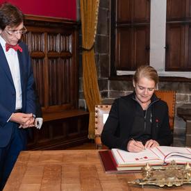 La gouverneure générale signe un livre d'or. Le maire de Mons, M. Elio di Rupo, est debout à sa droite et l'observe.