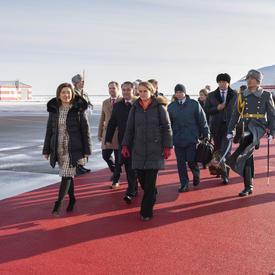 La gouverneure générale marche sur un tapis rouge qui mène à l'escalier d'un avion à l'arrière-plan.  Elle est entourée de représentants officiels.  Des gardes armés tapissent le tapis rouge.