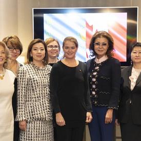La gouverneure générale pose avec un groupe de 9 femmes. Elles sont toutes debout. La gouverneure générale se trouve au centre.