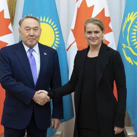 La gouverneure générale serre la main de Nursultan Nazarbayev, président du Kazakhstan.  Ils sourient pour la caméra.  Derrière eux se trouvent les drapeaux canadiens et kazakhs.