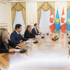 Un groupe de 8 personnes est assis autour d'une grande table oblongue.  La gouverneure générale Julie Payette et Nursultan Nazarbayev, Président du Kazakhstan, sont assis au milieu. À l'arrière-plan se trouvent des drapeaux.