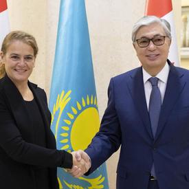 La gouverneure générale Julie Payette serre la main de Kassym-Jomart Tokayev, président du Sénat du Parlement de la République du Kazakhstan.  Ils sourient pour la caméra.  Derrière eux se trouvent les drapeaux canadiens et kazakhs.
