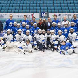 Deux équipes de hockey de jeunes posent sur la glace dans un aréna.  Les enfants portent des chandails blanc et bleu et de l'équipement de hockey. À l'arrière-plan, des adultes se tiennent debout, dont la gouverneure générale Julie Payette.