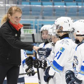 La gouverneure générale Julie Payette serre la main d'enfants habillés en tenue de hockey.  Ils sont sur la glace dans un aréna.