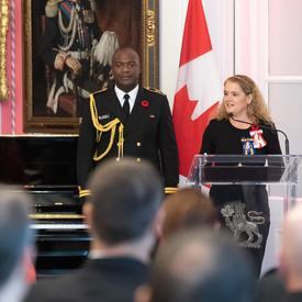 La gouverneure générale prononce une allocution debout devant un podium.  Derrière elle se trouve son aide de camp en uniforme de la Marine ainsi que le drapeau canadien.