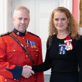 La gouverneure générale se tient aux côtés du récipiendaire le surintendant en chef Jeffery Joseph Adam, qui vient tout juste d'être investi au sein de l'Ordre du mérite des corps policiers.  Il porte l'insigne de l'Ordre sur son élan rouge.