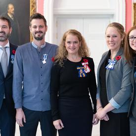 The Governor General stands between recipients Kahlil Baker, Samuel Gervais, Laura Howard and Brooke van Mossel-Forrester who are all wearing the Meritorious Service Cross (Civil Division) that they have just received.