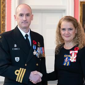 La gouverneure générale se tient aux côtés du Capitaine de frégate Jeffrey Lawrence Murray, qui porte, sur son uniforme naval, la Médaille du service méritoire (division militaire) qu'il vient de recevoir.