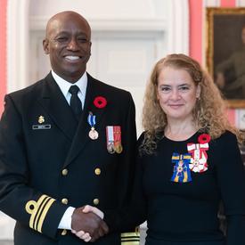 Le gouverneur général se tient à côté du lieutenant-commandant Paul Anthony Smith, qui porte, sur son uniforme naval, la Médaille du service méritoire (division militaire) qu'il vient de recevoir.