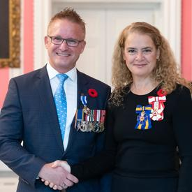 The Governor General stands next to recipient Chief Petty Officer 1st Class Adrew John Tiffin (Retired) who is wearing the Meritorious Service Medal (Military Division) he has just received.