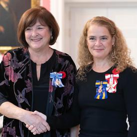 La gouverneure générale se tient à côté du récipiendaire Rachel Corneille Gravel, qui porte de la Médaille du service méritoire (division civile) qu'elle vient de recevoir.