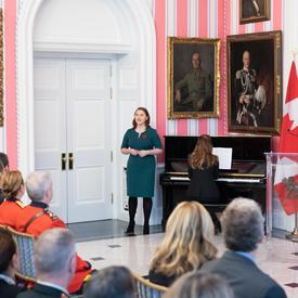 Le public regarde Tessa Fackelmann, mezzo-soprano locale, qui se tient à côté d'un piano et signe.  Son accompagnatrice, Danielle Girard, est assise au piano, dos au public.