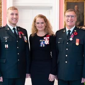 La gouverneure générale se tient entre le capitaine Michael Lawrence Kristy (retraité) et le caporal-chef Ryan Kristy qui portent la Médaille de la bravoure qu'ils viennent de recevoir sur leur uniforme militaire.